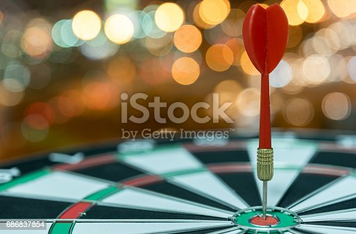 istock Dart target arrow on bullseye over bokeh background 686837854