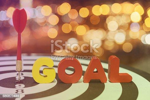 istock Dart target arrow on bullseye with goal words over bokeh background 686823434