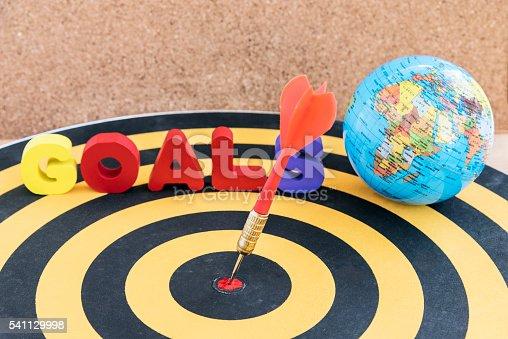 istock dart target in bullseye on dartboard with goals and globe 541129998