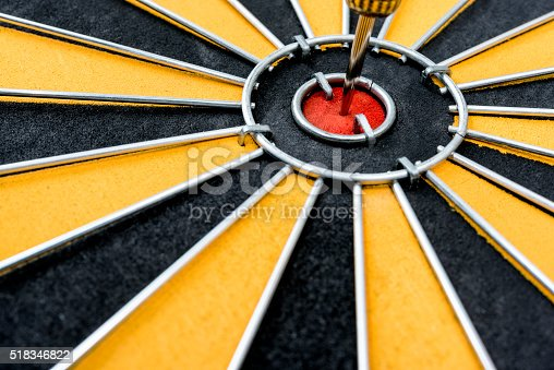 840201636 istock photo Dart target with arrow on the center of dartboard 518346822