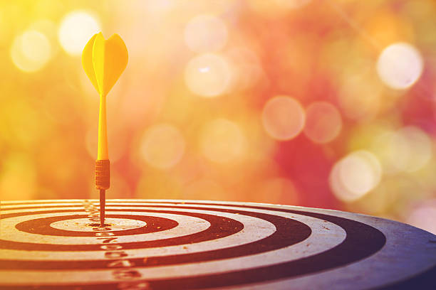 dart target with arrows over bokeh background - sports target stock photos and pictures