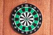 istock Dartboard hanging on wooden wall 1018138404