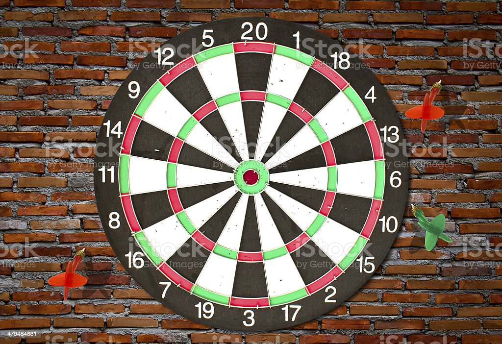 Dartboard on brick wall (Darts Hit Target) stock photo