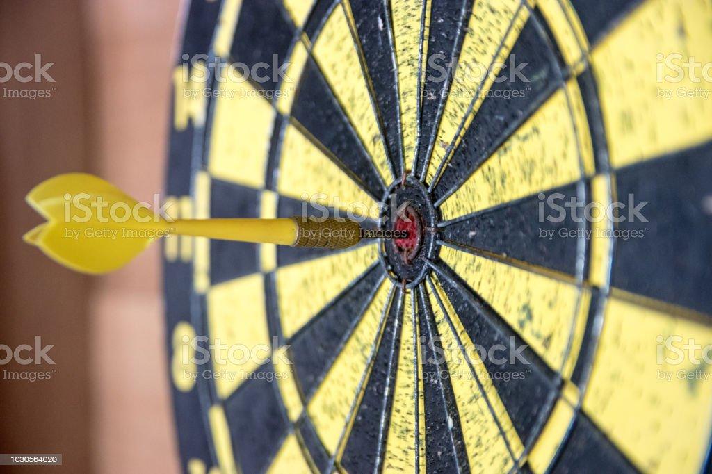 Dartboard with dart in bulls eye
