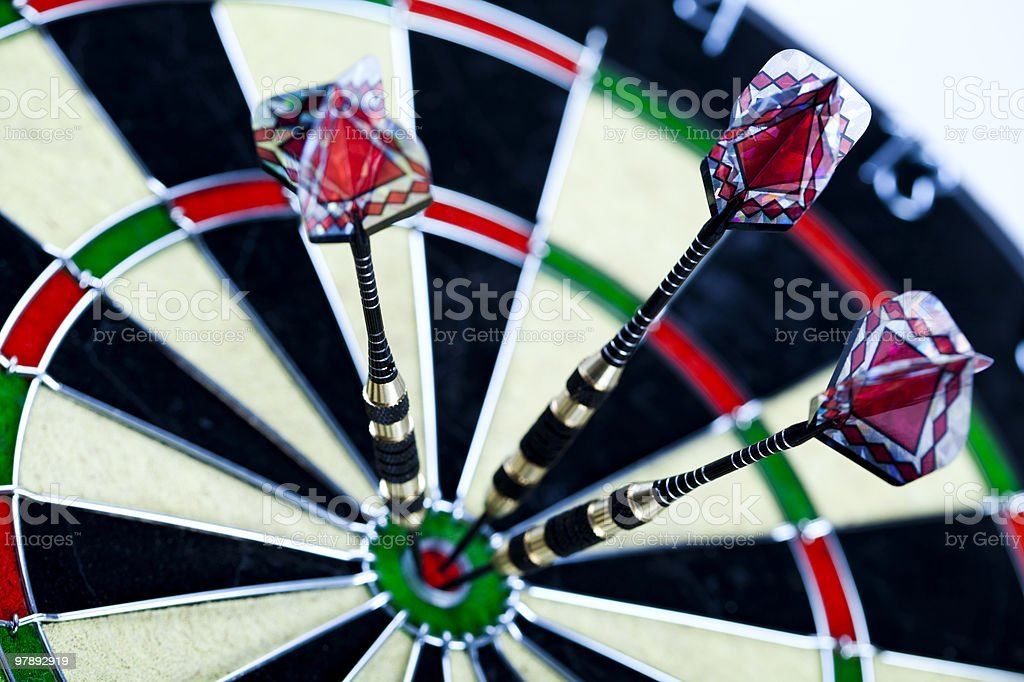 Dartboard with three darts in a bulls eye royalty-free stock photo