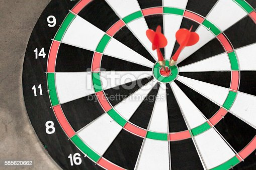 istock Darts accurately and perfectly hit the red spot on board 585620662