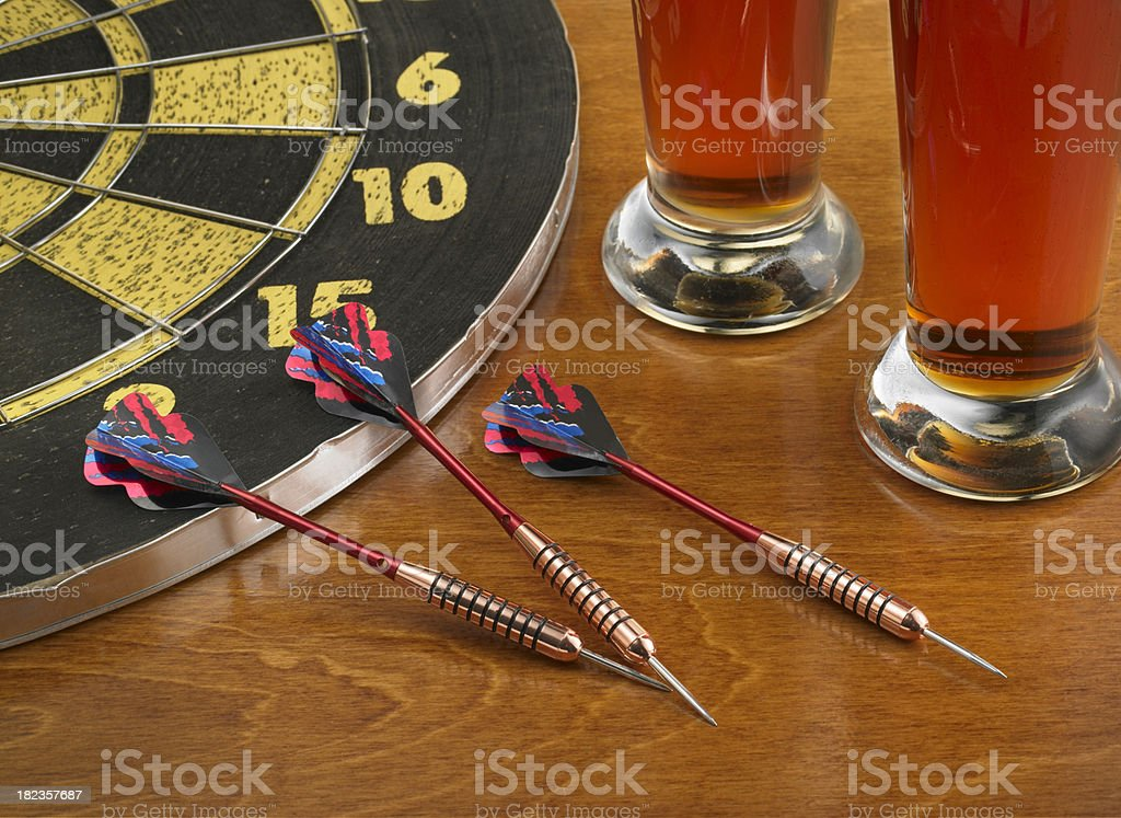 Darts laying on a bar with dartboard and beer royalty-free stock photo