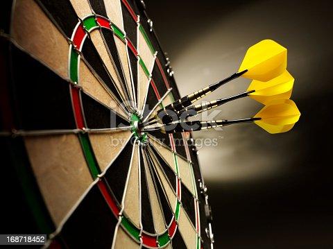 Three yellow darts hitting the target in a game of darts scoring a bulls eye.