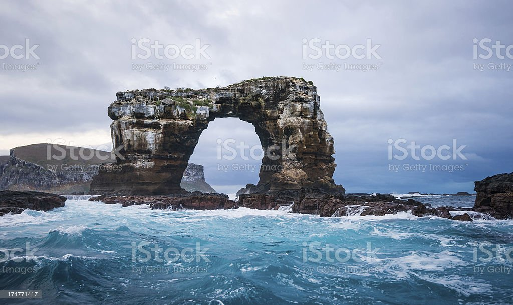 Darwin's Arch being hit by waves with Darwin island behind stock photo