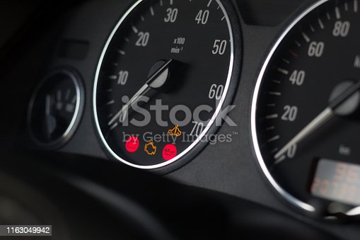 Dashboard indicators of usual car. Selective focus on tachometer. Service icons indicate to check engine, battery, oil pressure and maintenance distance. Arrows at zero.  Close up. Dark black design.