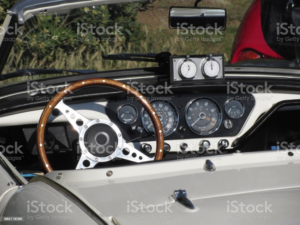 Dashboard of an old british classic car . Particular view of steering wheel and vehicle instrument panel . The car is a Triumph TR3 model produced between 1955 and 1962 stock photo