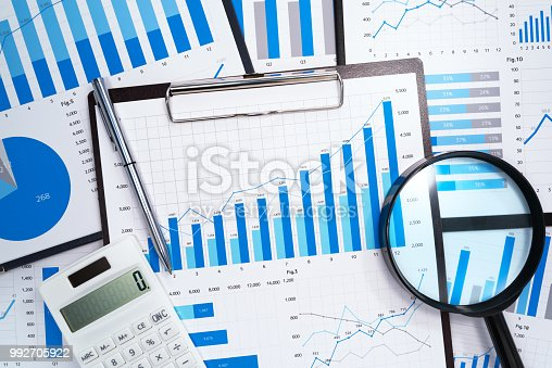 Many business reports. Magnifying glass,calculator and pen.