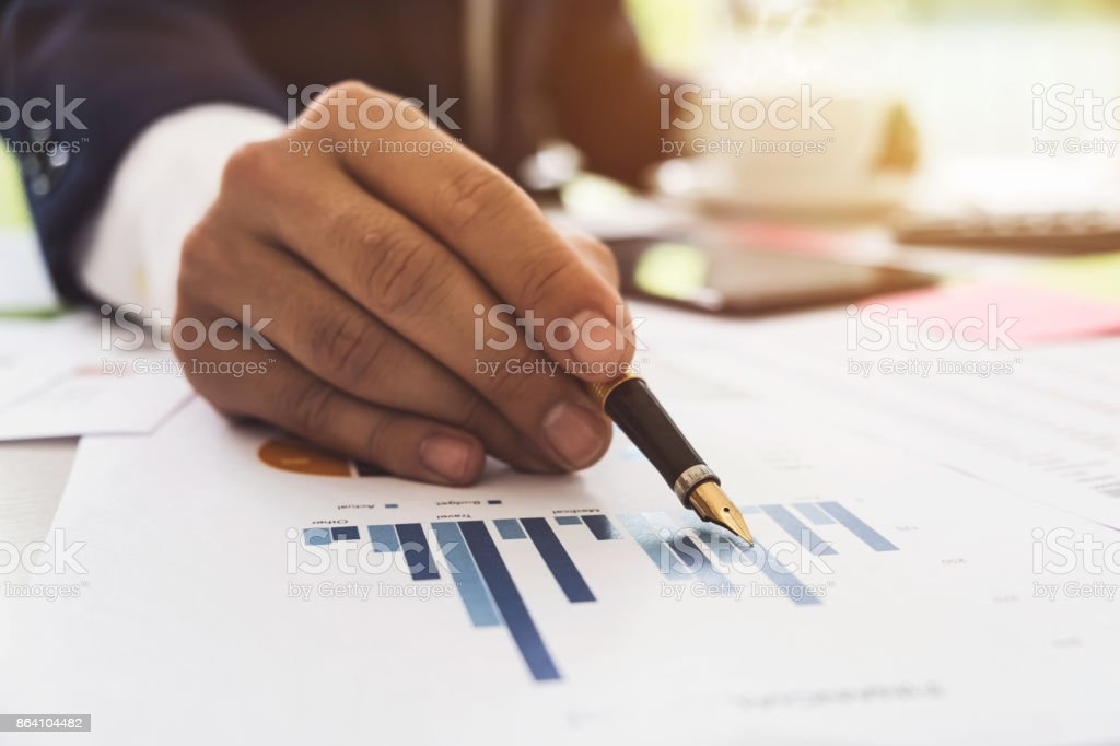 Data analyzing. Close up of business man adviser using pen pointing document report and discussing while hand holding a cup of coffee in his office royalty-free stock photo