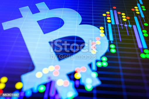istock Data analyzing in exchange stock market: the candle chars on display. Analytics price change cryptocurrency BTC to USD (Bitcoin / US Dollar), the most popular pair in the world. Big Bitcoin logo. 880801592