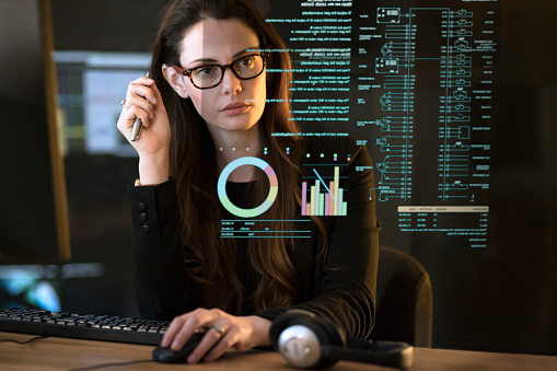 Stock photograph of a professional, good looking woman studying a see-through display showing a variety of data & information.