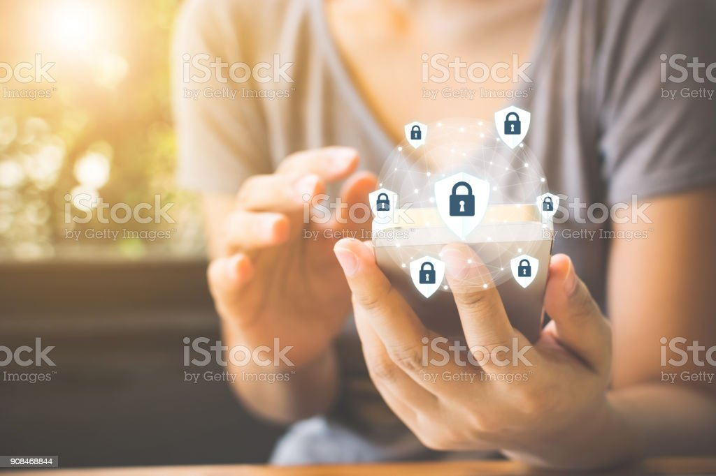 Data protection and security important information in your mobile phone, Woman hand using smartphone and icon key on shield stock photo