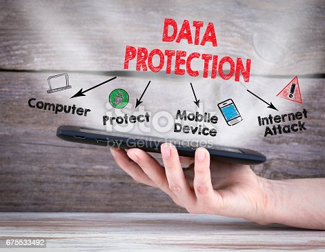 488497362istockphoto Data Protection. Tablet computer in the hand. Old wooden background 675533492