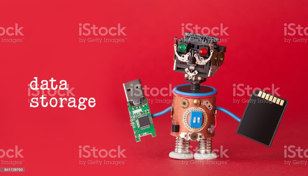 Data storage concept. Robot toy with usb flash stick and memory card on red background. Copy space macro view stock photo