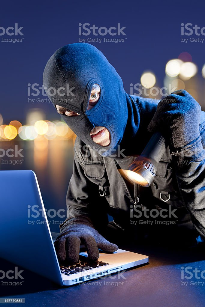 Data thief stealing DVD from laptop royalty-free stock photo