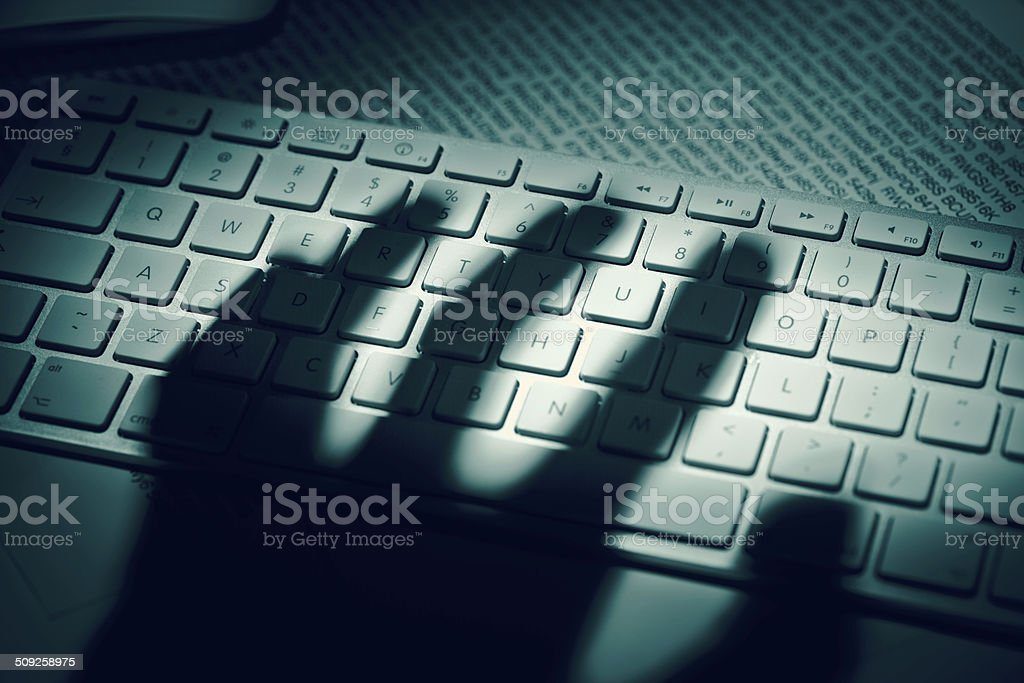 Data thief's hand shadow on computer keyboard stock photo