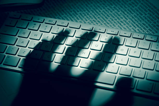 Data thief's hand shadow on computer keyboard A menacing hand'€™s shadow on a computer keyboard in front of printed computer data. Dramatic light, high contrast. threats stock pictures, royalty-free photos & images