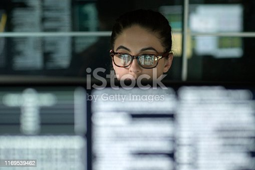 A young woman is surrounded by monitors & their reflections displaying scrolling text & data.