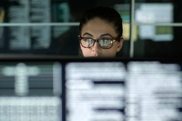 Data woman monitors A young woman is surrounded by monitors & their reflections displaying scrolling text & data. stock market stock pictures, royalty-free photos & images