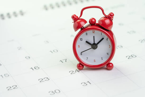 date and time reminder or deadline concept, small red alarm clock on white clean calendar with number of day, counting down to holiday, vacation or end of month - white background стоковые фото и изображения