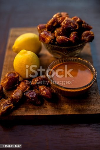 Date fruit face mask in a glass bowl consisting of some dates and lemon juice for oily skin. The Vertical well creative lit upshot of Date face mask for oily skin or Seborrhoea or seborrhea.