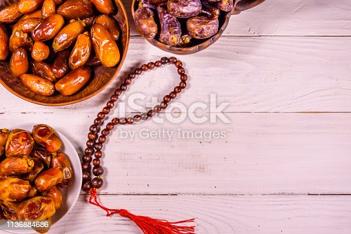 istock Date fruits and rosary on wooden table. Top view 1136884686