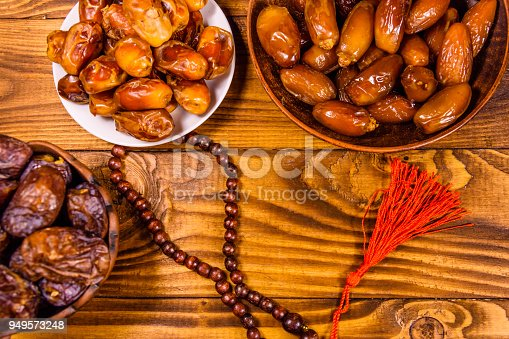 istock Date fruits and rosary on wooden table. Top view 949573248