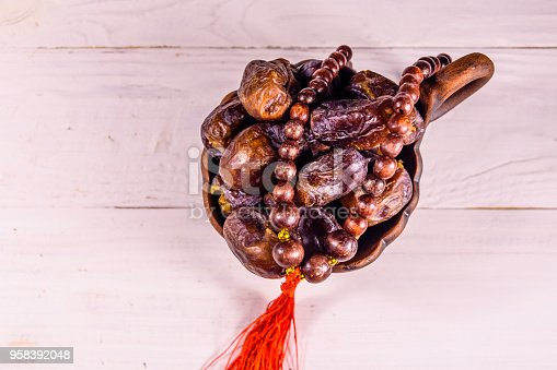 istock Date fruits and rosary on wooden table. Top view 958392048