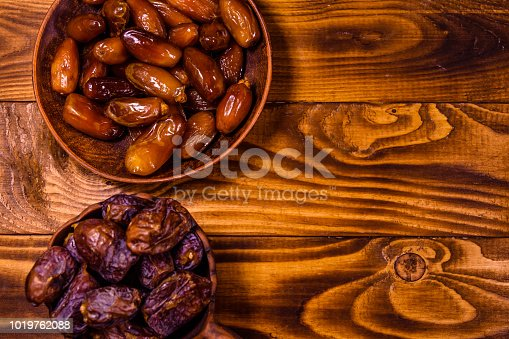 982465812 istock photo Date fruits on a wooden table. Top view 1019762088