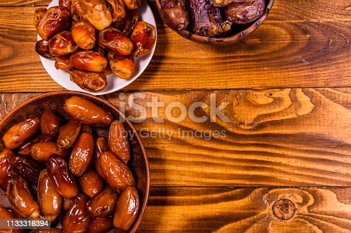 982465812 istock photo Date fruits on a wooden table. Top view 1133316394