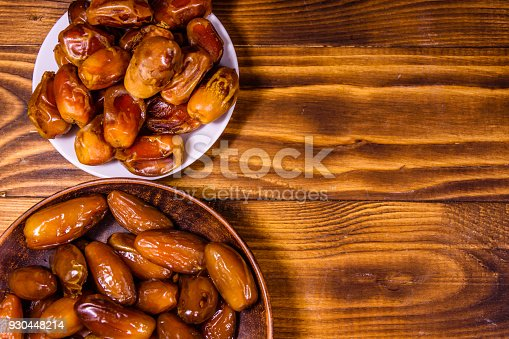 987444326 istock photo Date fruits on a wooden table. Top view 930448214