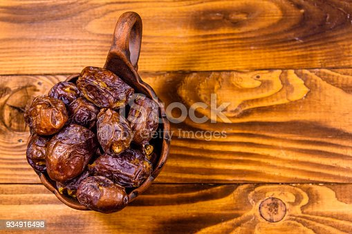 987444326 istock photo Date fruits on a wooden table. Top view 934916498