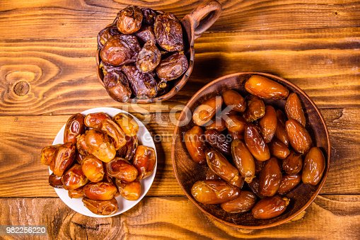 987444326 istock photo Date fruits on a wooden table. Top view 982256220