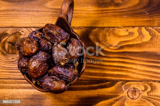 987444326 istock photo Date fruits on a wooden table. Top view 986301308