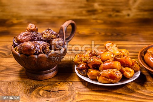 987444326 istock photo Date fruits on the rustic wooden table 937187306
