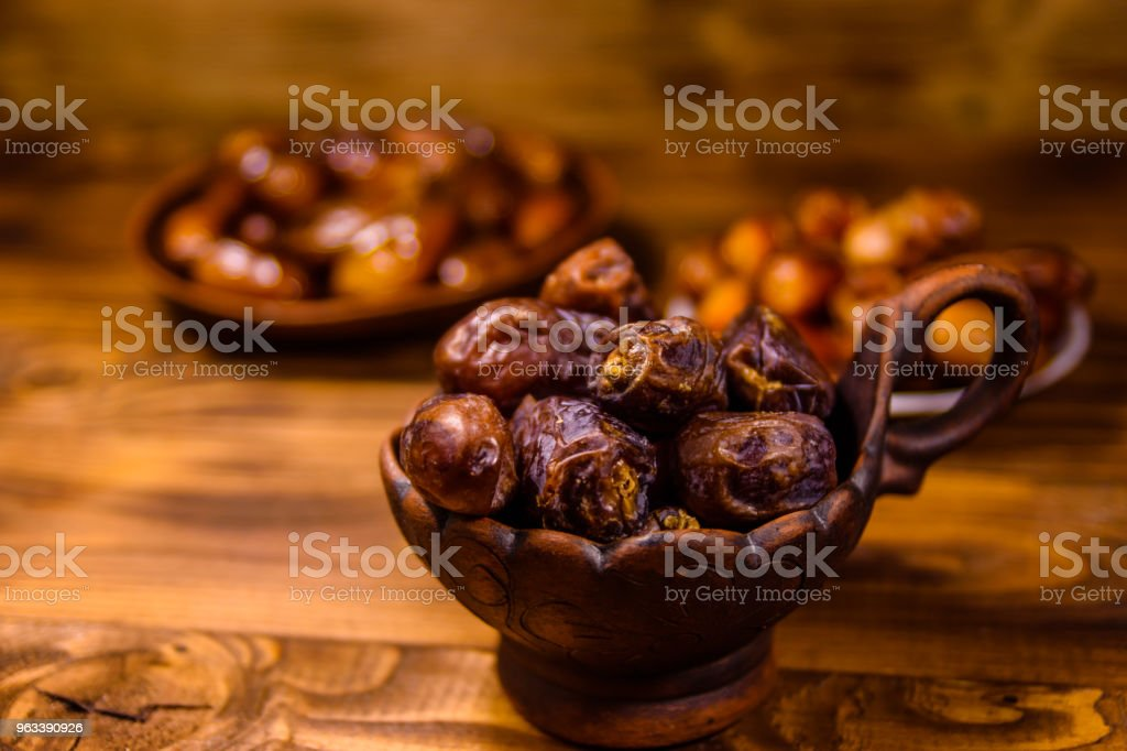 Date fruits on the rustic wooden table - Zbiór zdjęć royalty-free (Arabia)