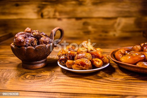 987444326 istock photo Date fruits on the rustic wooden table 990260536