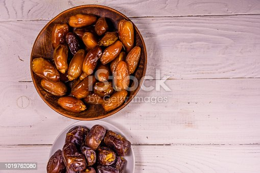 982465812 istock photo Date fruits on the white wooden table. Top view 1019762080