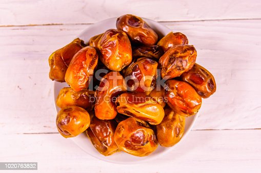 982465812 istock photo Date fruits on the white wooden table. Top view 1020763832