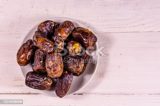 982465812 istock photo Date fruits on the white wooden table. Top view 1024506558