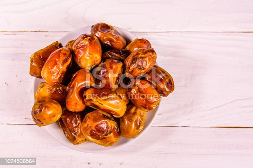 982465812 istock photo Date fruits on the white wooden table. Top view 1024506564