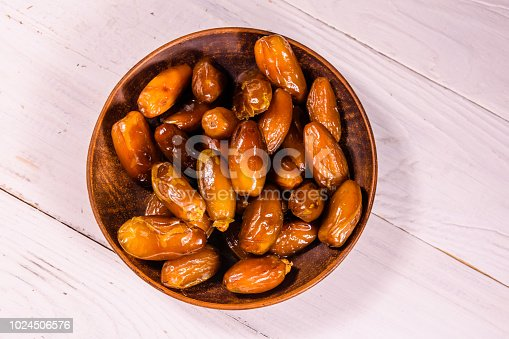 982465812 istock photo Date fruits on the white wooden table. Top view 1024506576