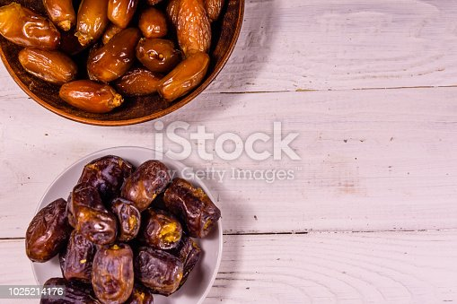 982465812 istock photo Date fruits on the white wooden table. Top view 1025214176