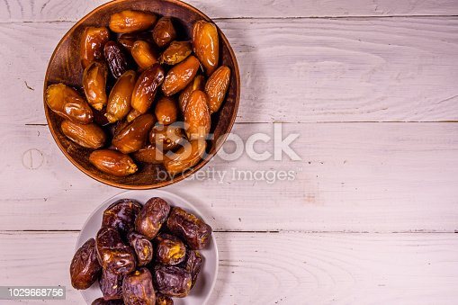 987444326 istock photo Date fruits on the white wooden table. Top view 1029668756