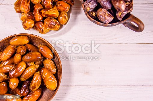 987444326 istock photo Date fruits on the white wooden table. Top view 934957266