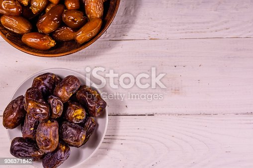987444326 istock photo Date fruits on the white wooden table. Top view 936371842